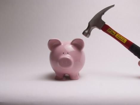 Money piggy bank breaking hammer